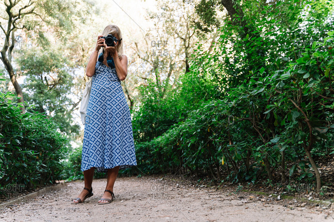 Woman in blue dress standing while taking a picture in a park