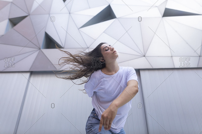 Young woman dancing with passion and energy in the street