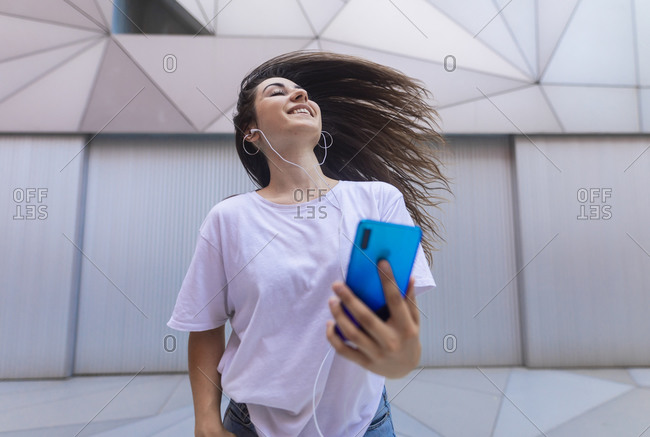 Young woman dancing on the street with headphones while moving her hair