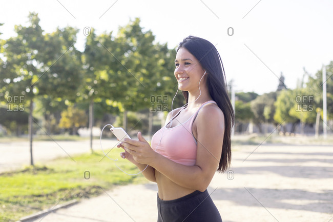 Athlete woman with mobile phone in hand before running