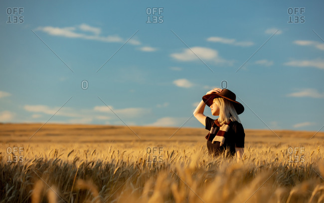 Blonde woman in black dress and hat with scarf in wheat field