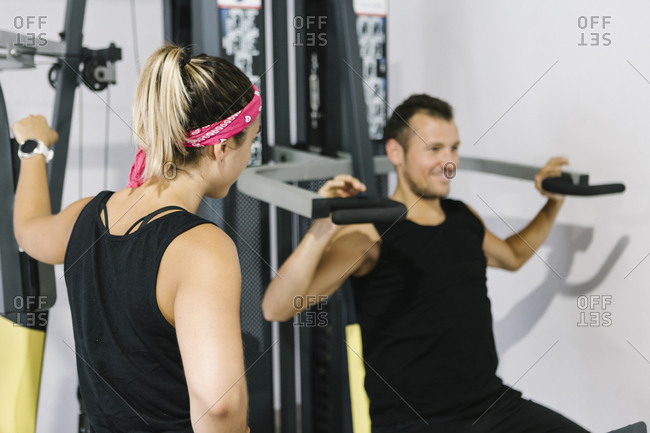 Fitness instructor with man working out in gym