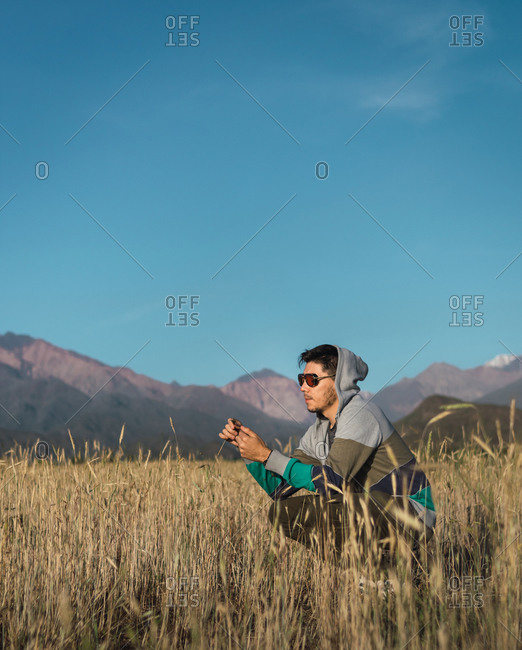 Young man sitting in a field next to the Andes mountains
