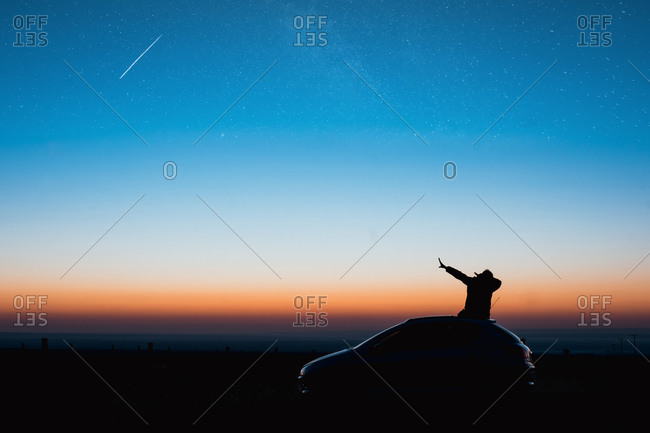 Young man sitting on car doing a Dub in the blue hour of sunrise