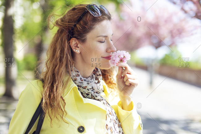 Woman smelling pink cherry blossom.