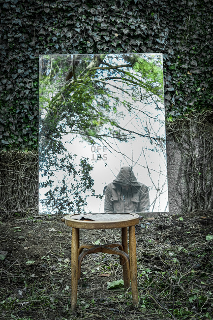 February 7, 2020: Poetic image of reflections in a garden and forest with a wooden chair in an atmosphere of a dream