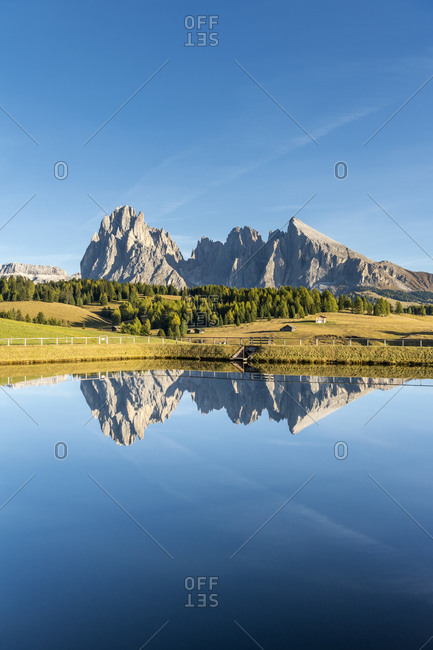 Alpe di Siusi, Castelrotto, South Tyrol, Bolzano province, Italy, Europe. The Sassolungo massif is reflected in a lake on the Alpe di Siusi