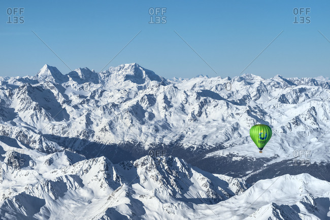 January 5, 2020: South Tripoli, Italy, Europe. Crossing the Alps in a hot air balloon. The balloon in front of the peaks of the Ortler group with Konigspitze, Zebru and Ortler
