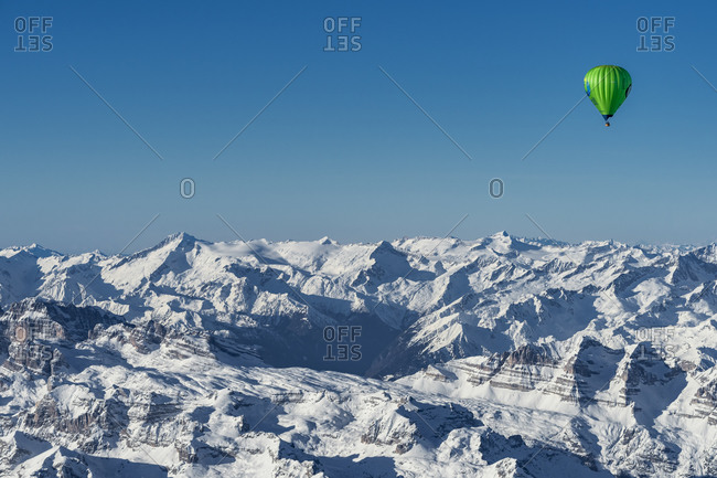 January 5, 2020: Adamello group, Trentino, Italy, Europe. Crossing the Alps in a hot air balloon. The balloon over the peaks of the Brenta group, in the background the Adamello group