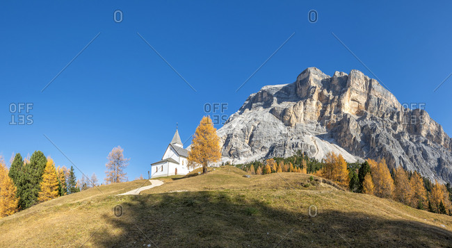 Hochabtei, Alta Badia, Bolzano province, South Tyrol, Italy, Europe. The pilgrimage church of Heilig Kreuz and the rock walls of the mighty Kreuzkofel