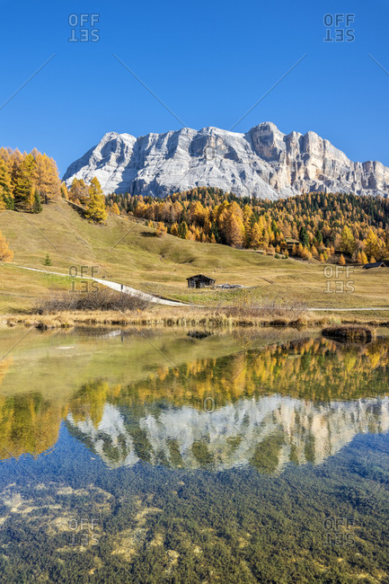 Hochabtei, Alta Badia, Bolzano province, South Tyrol, Italy, Europe. Autumn in the Armentara meadows. The peaks of the Zehnerspitze and the Heiligkreuzkofel are reflected in a small mountain lake