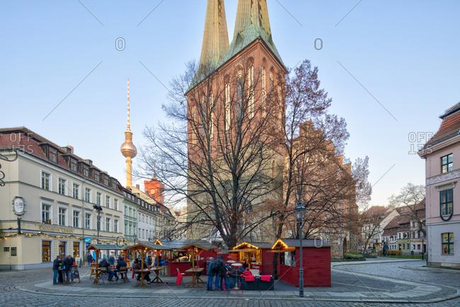 December 5, 2019: Nikolaikirche, winter market with Feuerzangenbowle, blue hour, Nikolaiviertel, Berlin's historic center, Berlin, Germany