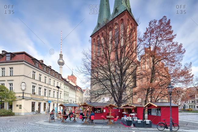 December 3, 2019: Nikolaikirche, winter market with Feuerzangenbowle, Nikolaiviertel, Berlin's historic center, Berlin, Germany