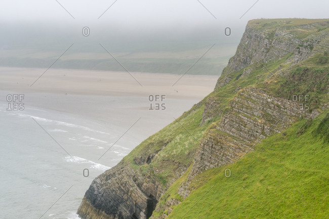 A huge wide beach on The Gower Peninsula under a thin layer of mist in Wales