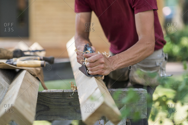 A man using a wood plane on a timber outdoors