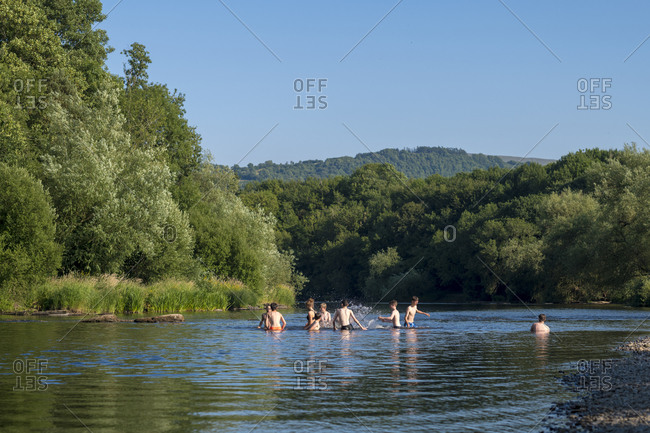 Hay-on-Wye, Wales - July 6, 2018: Children play in the Wye River in summertime