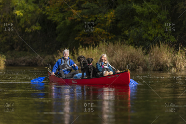 Hay-on-Wye, Wales - October 3, 2018: A couple and their dogs in a canoe on the River Wye