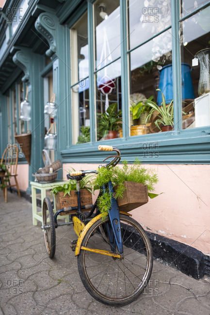 Hay-on-Wye, Wales - September 17, 2019: A bike outside an antique shop holding plants