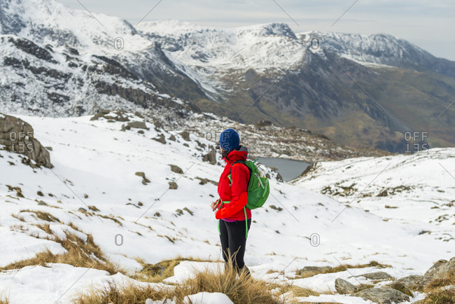 Hiking in the snow towards the top of Tryfan looking towards the Glyder mountain range in the distance and Llyn Ogwen below