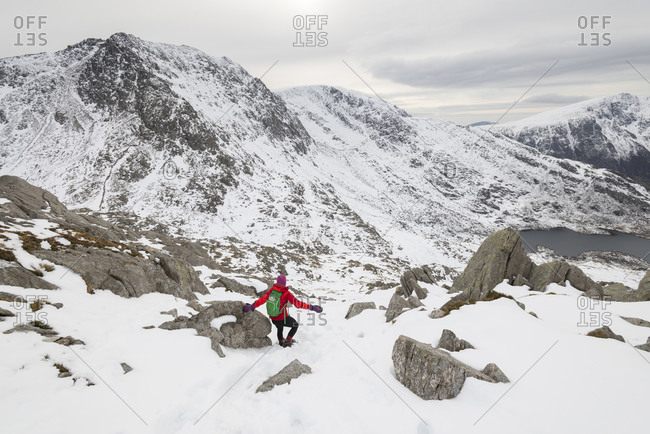 Hiking in deep snow from the top of Tryfan and the Glyders with a view of little Llyn Bochlwyd below