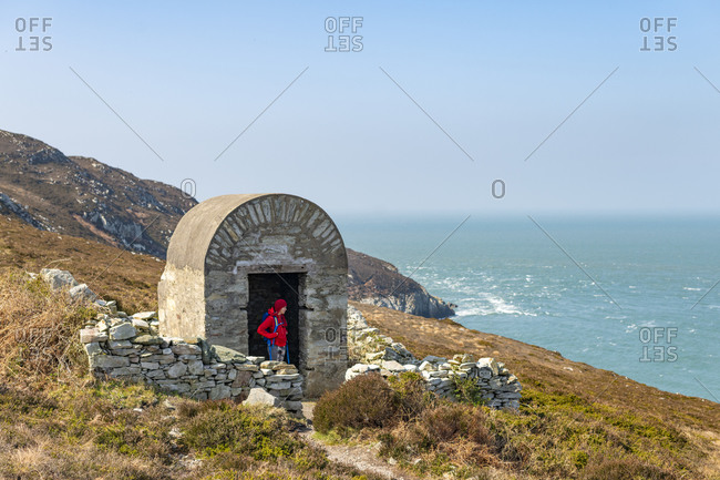 A woman hiking along a coastal path in Anglesey stands near an old enclosure