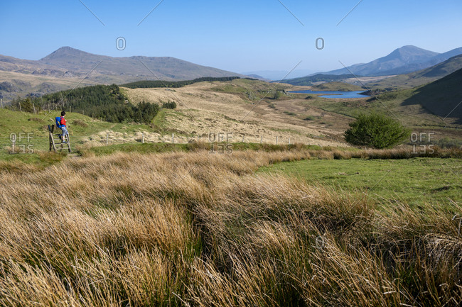 A woman walking in Snowdonia stops on top of a Stye to look at the view of a lake and mountains near Rhyd-Ddu