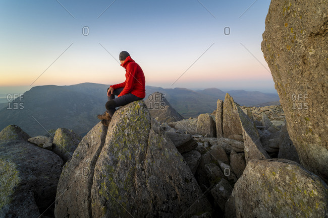 Man looking out over Snowdonia from the top of Glyer Fach with mount Snowdon in the distance
