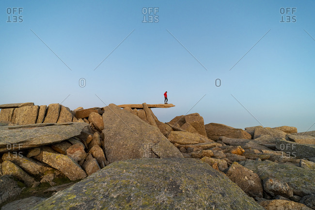 Man walking on top of the Cantilever stone on the summit of Glyer Fach in Snowdonia