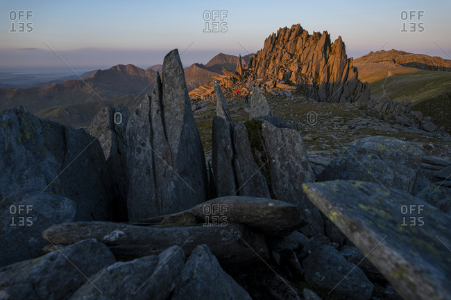 Rock formation on top of Glyer Fach in Snowdonia known as The Castle with mount Snowdon in the distance