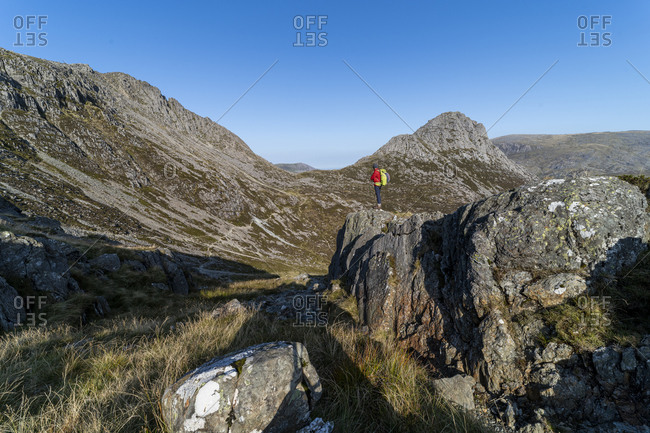 Man trekking from the summit of Glyder Fach in Snowdonia with a view of Tryfan in the distance