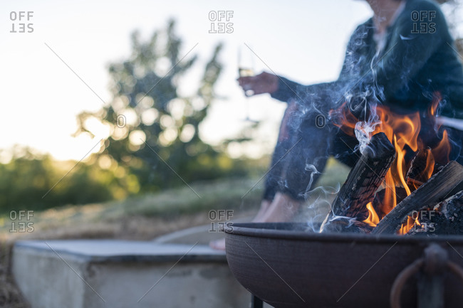 A girl has a glass of Champagne next to a fire pit