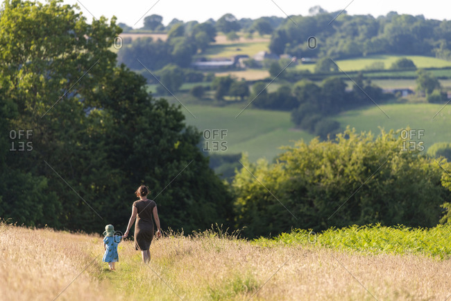 A mother and baby walk through a field in the countryside holding hands