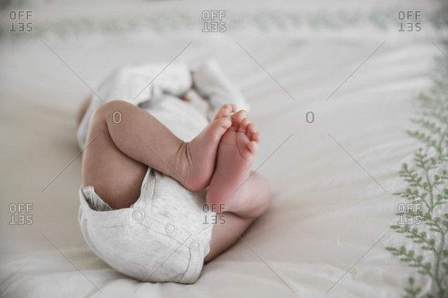 Close up a baby lying on white blanket with bare feet
