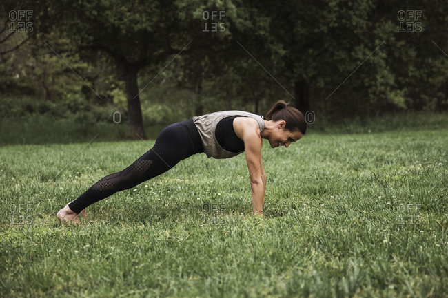 Profile view of woman in black yoga pants doing plank pose outdoors
