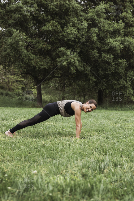 Woman in black yoga pants doing plank pose outdoors