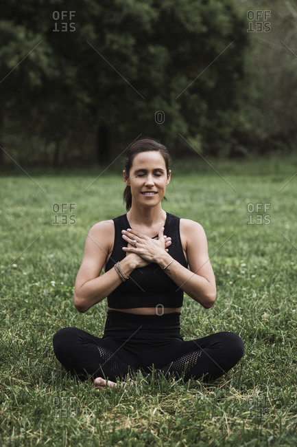 Woman siting in a field doing yoga