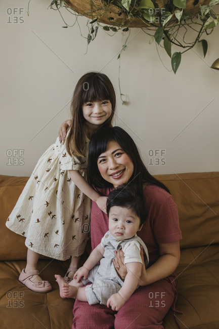 Mom sitting on sofa with her baby boy and daughter