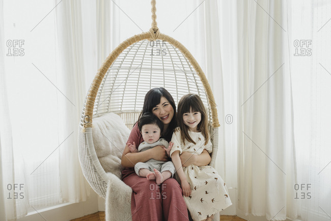 Mom sitting in hanging chair with her baby boy and daughter