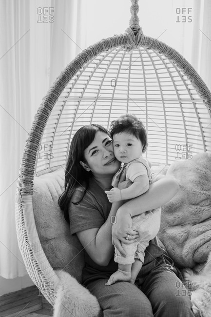 Mom and baby boy sitting in chair swing in black and white