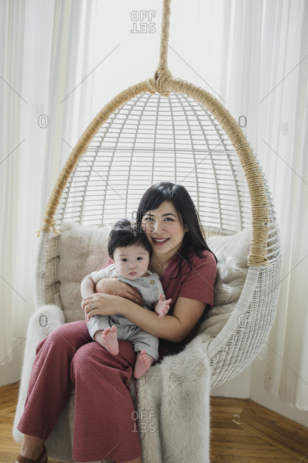 Portrait of a mother sitting with her baby boy in chair swing