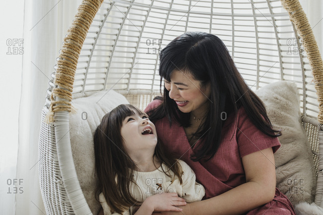 Mother playing and swinging in chair swing inside with daughter