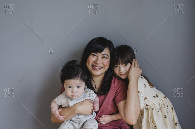 Mother holding baby boy and hugging daughter in front of gray background