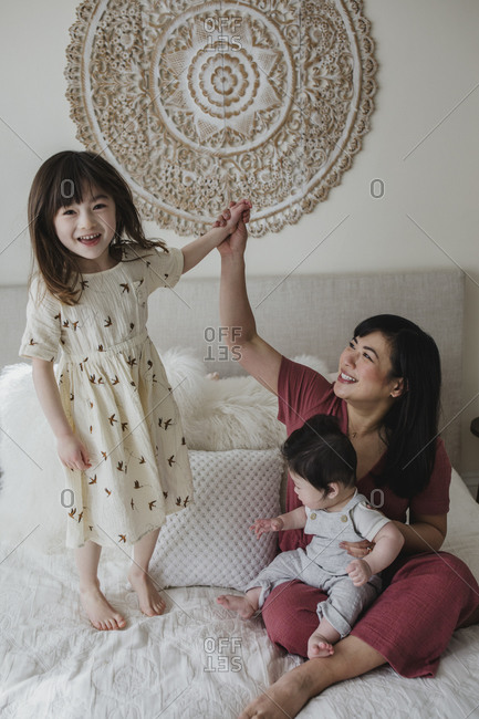 Mom sitting on bed playing with her baby boy and daughter