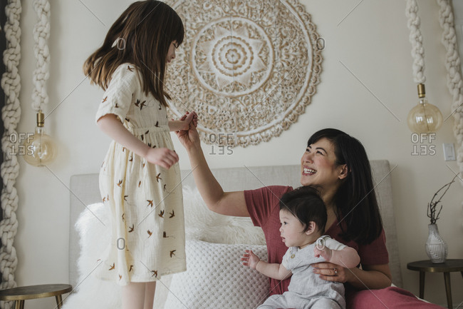 Girl jumping on bed beside mother and baby brother