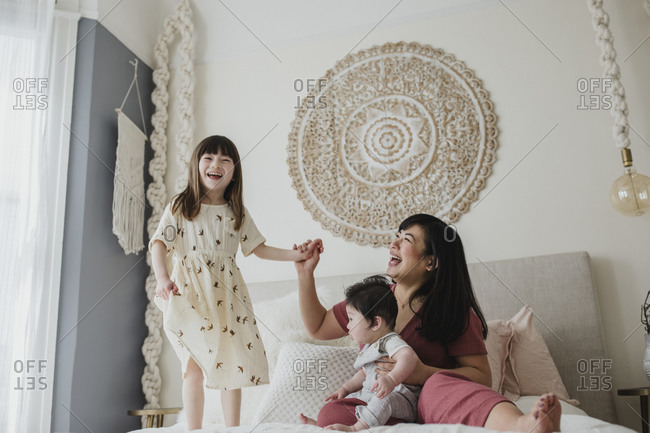 Little girl jumping on bed beside mother and baby brother