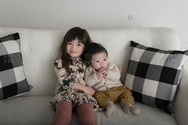 Sister sitting with arm around baby brother on white sofa