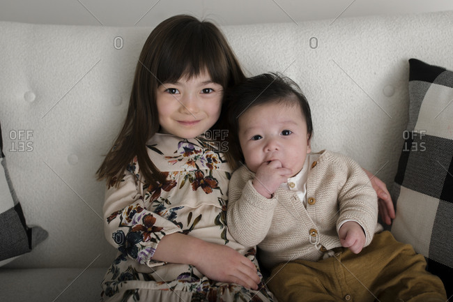Portrait of sister sitting with arm around baby brother on white sofa