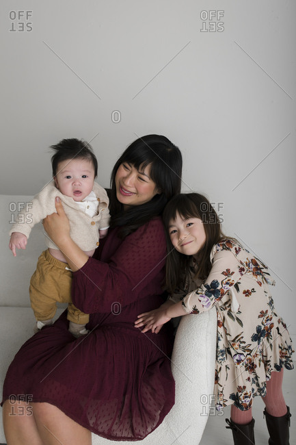 Asian woman sitting on sofa with her baby boy and daughter