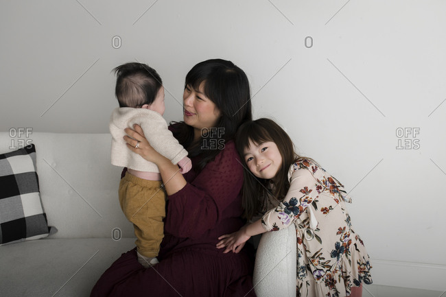 Asian woman sitting on white couch with her baby boy and daughter