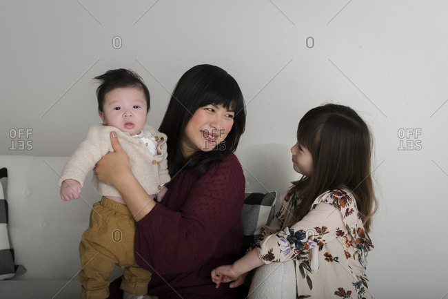 Asian woman on white couch holding her baby boy and looking at daughter